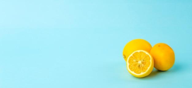 Zomer en vitaminen achtergrond banner. citroen op een blauwe achtergrond, minimaal voedselconcept