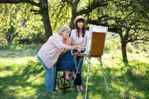 Zomer familie vrije tijd met hobby schilderen. buitenportret van een gezin van drie generaties vrouwen, tijd doorbrengend buiten in het park, samen tekenend op canvas met verf.