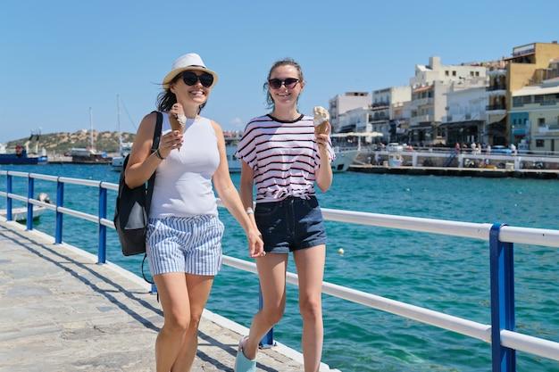 Zomer familievakantie, moeder en dochter tiener lopen samen eten van ijs