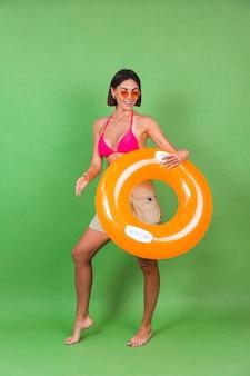 Zomer fit sportieve vrouw in roze bikini en fel oranje opblaasbare ring rond en zonnebril op groen, blij vrolijk opgewonden blij positief