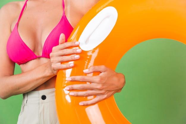 Zomer fit sportieve vrouw in roze bikini en fel oranje opblaasbare ring rond en zonnebril op groen, geen hoofdschot