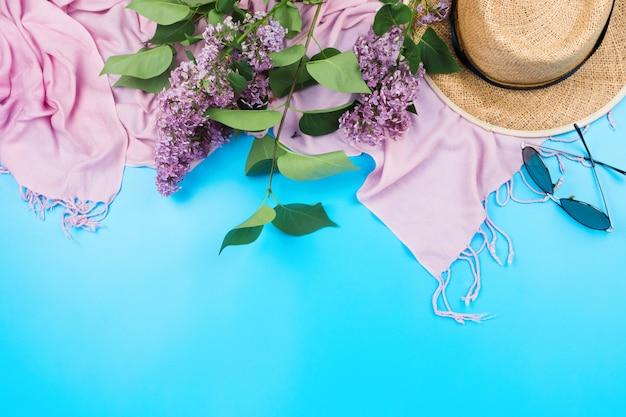 Zomer flatlay met roze sjaal, strohoed en zonnebril op blauw