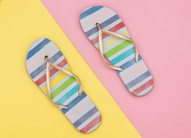 Zomer flip flops sandaal op gele en roze achtergronden.