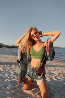 Zomer foto van sexy blonde vrouw in groene crop top en jeans poseren op tropisch strand.