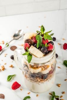 Zomer fruit bessen ontbijt. gezond bananensplit ontbijt met roomkaas, frambozen, bramen, mint, witte en roze chocolade. in stenen pot, marmeren tafel. kopieer ruimte dichtbij bekijken