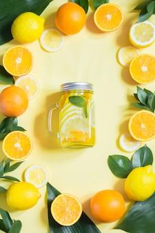 Zomer fruit water met citroen, sinaasappel, munt en ijs in stenen pot op geel. tropisch concept.