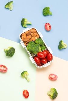 Zomer gezond voedselconcept: kader met lunchdoos en gemengd van vruchten op blauwe achtergrond; bovenaanzicht, plat gelegd