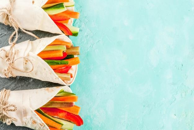 Zomer gezonde snack, mexicaanse stijl tortilla sandwich wraps geassorteerde kleurrijke verse groentestokken (selderij, rabarber, peper, komkommer en wortel) met yoghurtsaus dip lichtblauwe achtergrond