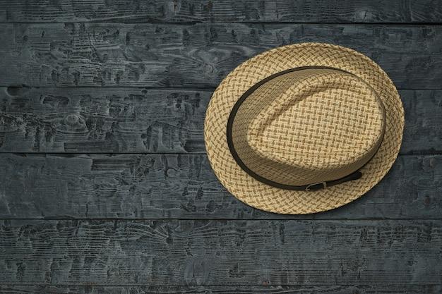 Zomer heren hoed op een zwarte houten tafel. klassieke hoofdtooi voor heren.
