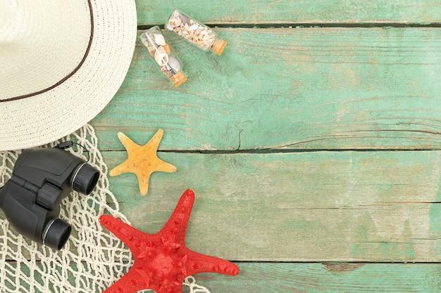 Zomer houten zee reizen achtergrond met hoed verrekijker zee verrekening en zeesterren