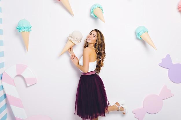 Zomer, ijsdroom, aantrekkelijk modieus model in geïsoleerde tule rok. plezier hebben, glimlachen, echte positieve emoties uiten.
