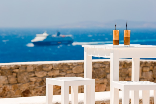 Zomer ijskoffie frappuccino, frappe of latte in een groot glas in strandbar