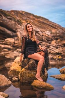 Zomer jonge brunette blanke vrouw in een lange zwarte transparante jurk op sommige rotsen in de buurt van de zee op een zomermiddag. zittend op een rots glimlachend en weerspiegeld in het water