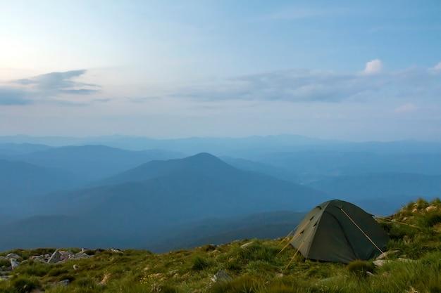 Zomer kamperen in de bergen bij zonsopgang. de toeristentent op ronde grasrijke heuvel op verre mistige blauwe bergen strekt zich onder roze hemel vóór zonsopgang of zonsondergang uit. toerisme, wandelen en schoonheid van de natuur concept.