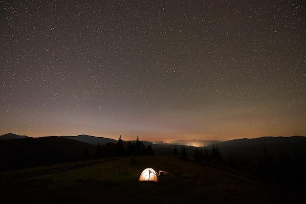 Zomer kamperen 's nachts. toeristische tent en brandend kampvuur op groene vallei onder donkere sterrenhemel.