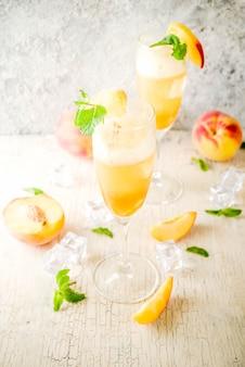 Zomer koude alcoholische drank, ijs perzik bellini cocktail met muntblaadjes, licht betonnen oppervlak