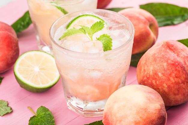 Zomer koude alcoholische drank, ijs perzik bellini cocktail met muntblaadjes,