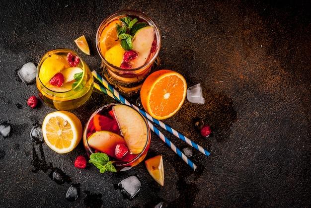 Zomer koude cocktail set van drie fruit en bessen sangria drankje. rood wit roze met appel, citroen, sinaasappel en framboos