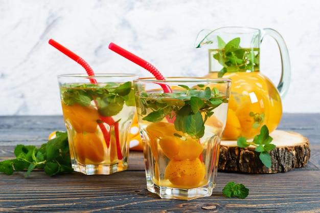 Zomer koude drankjes. heerlijk verfrissend drankje met abrikoos en munt in glazen op een houten tafel. compote van fruit. selectieve aandacht.