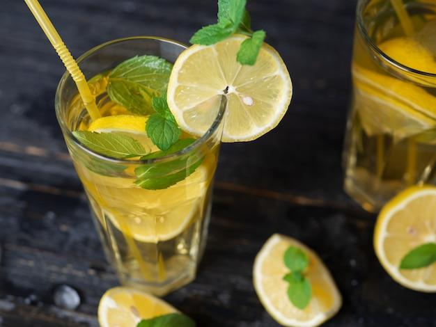 Zomer koude zelfgemaakte mojito-thee met munt en citroen en ijs