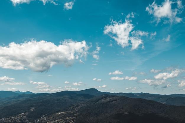 Zomer landschap in bergen en de donkerblauwe lucht met wolken
