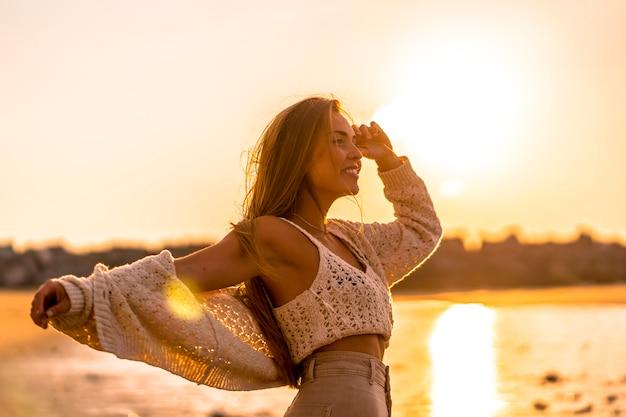 Zomer levensstijl. een jonge blonde blanke vrouw in een witte korte wollen trui op een strand zonsondergang. met open armen uitkijkend op zee