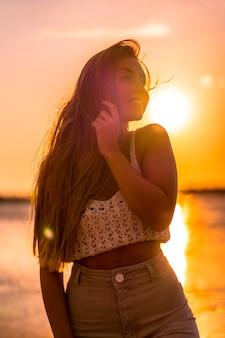 Zomer levensstijl. een jonge blonde blanke vrouw in een witte korte wollen trui op een strand zonsondergang