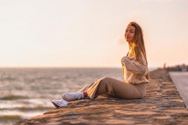 Zomer levensstijl, een jonge blonde blanke vrouw zitten aan zee in een witte crop top en corduroy broek. camera kijken glimlachen