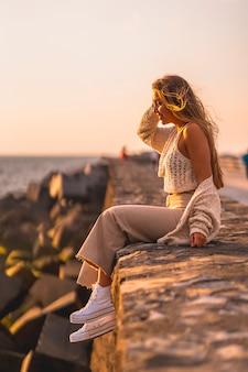 Zomer levensstijl, een jonge blonde blanke vrouw zitten aan zee in een witte crop top en corduroy broek. genieten van een winderige zomermiddag