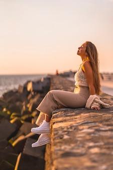 Zomer levensstijl, een jonge blonde blanke vrouw zitten aan zee. met gesloten ogen genieten van de zomermiddag en frisse lucht inademen