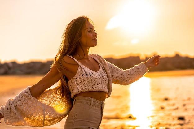 Zomer levensstijl, een jonge blonde met steil haar, het dragen van een kleine wollen trui en corduroy broek op het strand. genieten van de zon bij zonsondergang aan zee