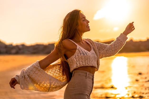 Zomer levensstijl, een jonge blonde met steil haar, het dragen van een kleine wollen trui en corduroy broek op het strand. genieten van de zon bij zonsondergang