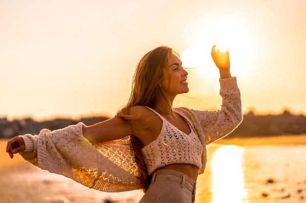 Zomer levensstijl, een jonge blonde met steil haar, het dragen van een kleine wollen trui en corduroy broek op het strand. genieten van de zon