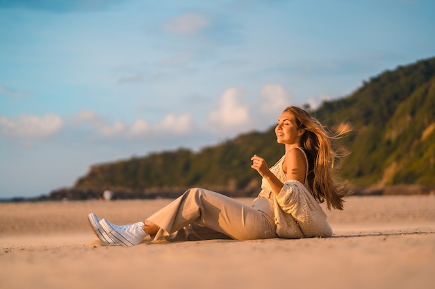 Zomer levensstijl, een jonge blonde met steil haar, in een kleine wollen trui en corduroy broek zittend op het strand met bergen. genieten van de zachte zeebries