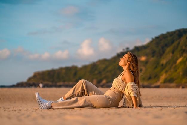 Zomer levensstijl, een jonge blonde met steil haar, in een kleine wollen trui en corduroy broek zittend op het strand met de zee. met gesloten ogen genieten van de zee bij zonsondergang