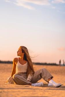 Zomer levensstijl, een jonge blonde met steil haar, in een kleine wollen trui en corduroy broek zittend op het strand. zittend op het zand naar links kijkend met de zeebries