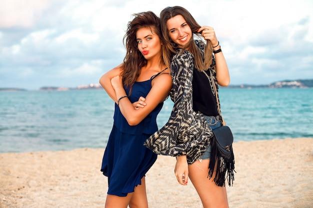 Zomer levensstijl mode portret van jonge vrouwen in stijlvolle outfits, wandelen in de buurt van de oceaan, positieve stemming, vintage getinte kleuren.