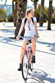 Zomer levensstijl portret van gelukkig vreugdevolle blonde hipster meisje, sportieve fit dagen, vintage roze fiets rijden, reizen met rugzak op exotisch land, plezier buitenshuis, palmen, park, natuur.