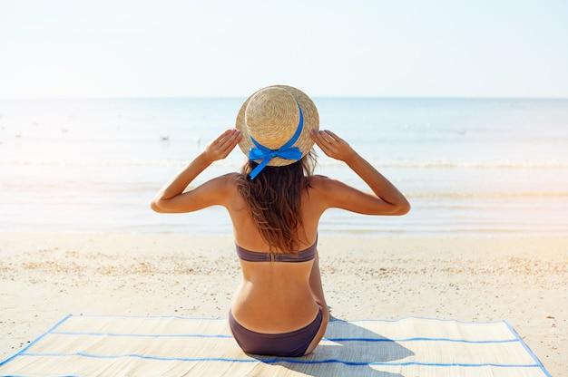 Zomer levensstijl portret van mooie jonge suntanned vrouw in een hoed