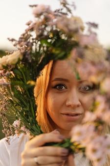 Zomer levensstijl portret van mooie jonge vrouw in een krans van wilde bloemen krans op zijn hoofd