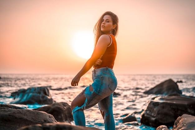 Zomer levensstijl, sexy look van een jonge vrouw in een rood shirt op een zonsondergang aan zee