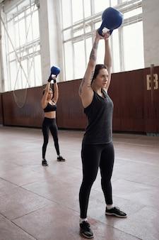 Zomer lichaamsvoorbereiding. jonge blanke vrouwen in zwarte activewear trainen met kettlebells in grote sporthal