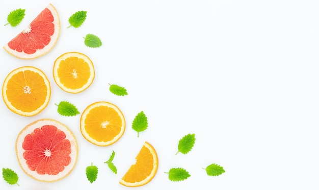 Zomer lichte achtergrond met sinaasappels, grapefruits en groene bladeren op het grijze oppervlak en plaats voor tekst