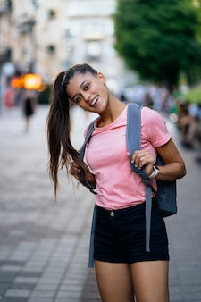 Zomer lifestyle mode portret van jonge stijlvolle hipster vrouw die op straat loopt