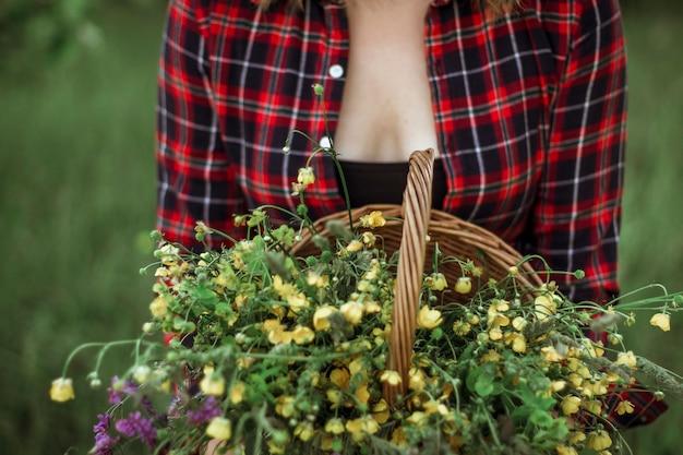 Zomer lifestyle portret van een mooie jonge vrouw die lacht en een mand vasthoudt met een boeket wilde bloemen. het concept van geluk en liefde. foto zonder hoofd