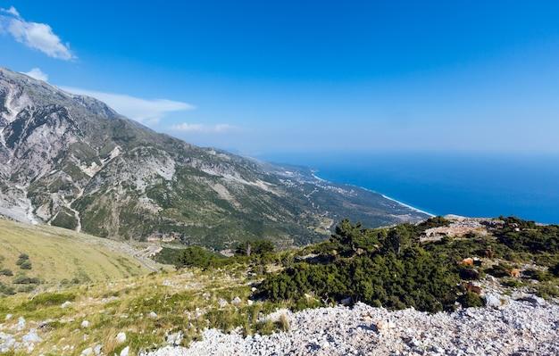 Zomer llogara pas uitzicht met weg, kudde geiten op helling en zeewateroppervlak (albanië)