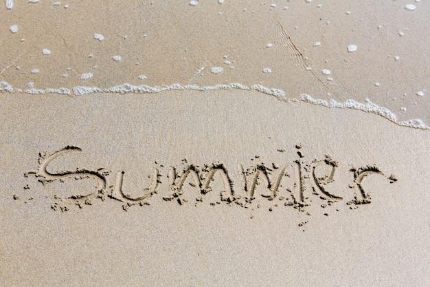 Zomer met de hand geschreven inschrijving in zand op een strand