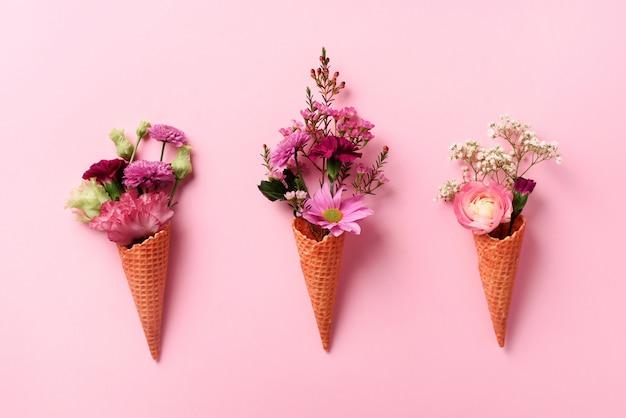Zomer minimaal concept. roomijskegel met roze bloemen en bladeren op punchy pastelkleurachtergrond.