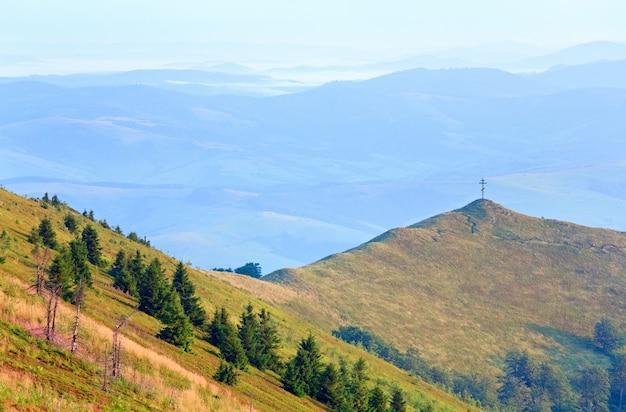 Zomer mistige berglandschap met christelijk kruis bovenop (oekraïne, karpaten)