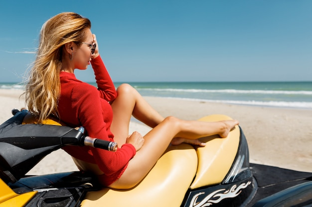 Zomer mode foto van sexy blonde vrouw in rode outfit zittend op gele water scooter over tropisch strand.